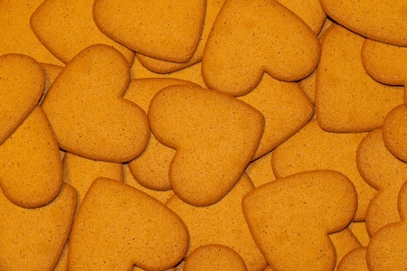 A background of heart formed gingerbread biscuits, rather close-up. photo