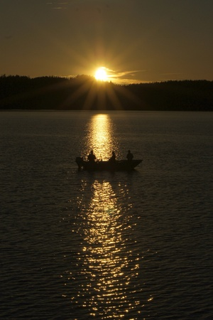 Three men in a fishing boat at the sunset. Just silhouttes of the men and trees in the background. photo