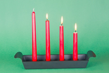 Candlestick in dark metal with three red candles lighted. photo