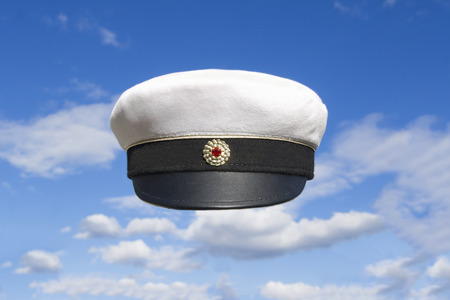 education in sweden: Swedish student cap front view on blue sky with some clouds  Red marking and gold ribbon  Stock Photo