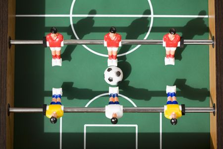 playing tabletop soccer with red and yellow figures photo