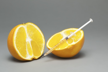 chemical peels: Orange gets an orange substance injected from hand with gloves