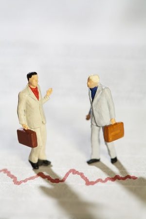 Teamwork And Discussion, two miniature model businessmen having a deep discussion above a red line graph. Stock Photo - 11694639