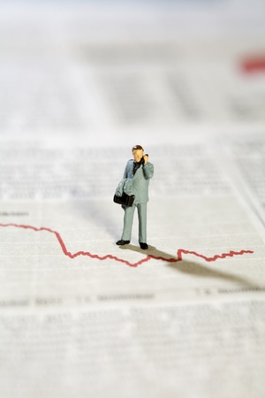 Miniature Model Businessman And Graph on the telephone discussing the statistics. Stock Photo - 11694643