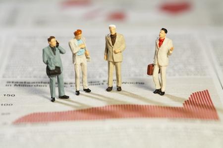 bar graph: Teamwork And Analysis, four miniature businessmen standing analysing performance above a red bar graph.