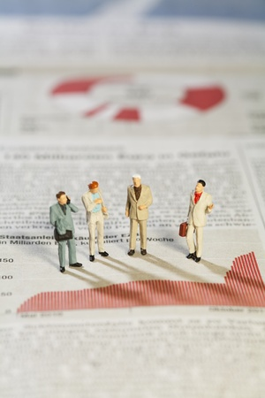 miniature people: Business Strategy Meeting, four miniature models of businessmen standing above a bar graph as though in a meeting. Stock Photo