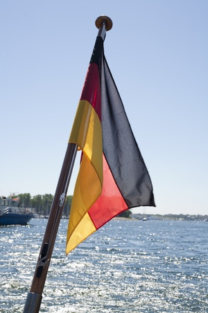 german ocean: German Flag Flying Over Ocean from a flagpole with coastline in background.