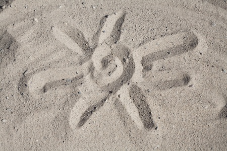 Finger Drawing Of Sun In Beachsand, a reminder of a summer holiday. Stock Photo