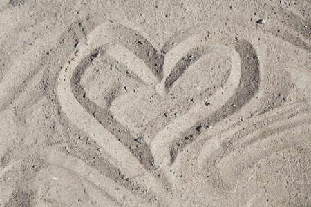 Romantic Heart Washed by Waves, a simple line drawing of a heart in sand, conceptual for romance, marriage and Valentines.