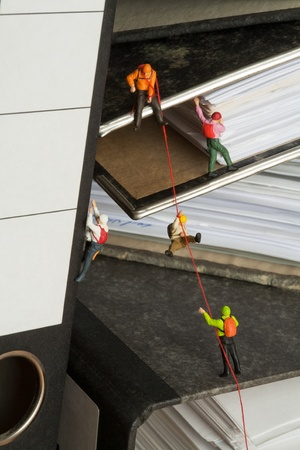 Miniature Mountaineers Climbing Office Files, miniature models of mountaineers rope climbing up a set of randomly positioned files. Stock Photo