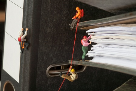 Miniature people group of climbers ascending document binders photo
