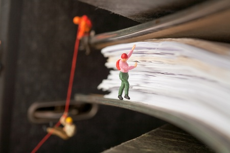 Miniature people group of climbers ascending document binders Stock Photo - 11694661