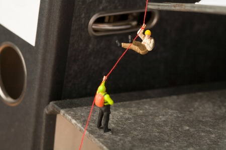 Abseiling On Office Files, miniature models of mountaineers abseiling down off an office file.