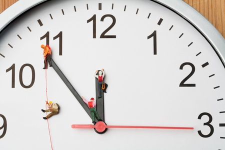 Four miniature people climbers ascending clock hands. Stock Photo