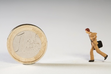 In Support Of The Euro, a miniature model businessman running towards an upright Euro coin to offer support.