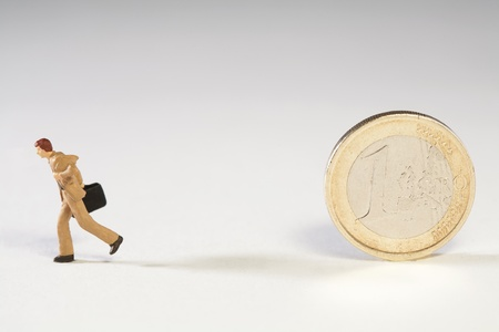 abandoning: Abandoning The Euro, a miniature model businessman running away from an upright Euro coin with his briefcase Stock Photo