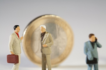 The Euro Crisis, closeup of worried miniature model businessmen in discussion near a Euro coin. photo