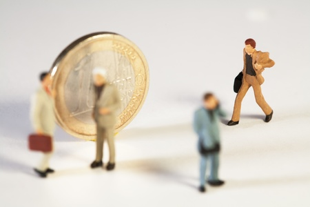 Coming To The Aid Of The Euro, a miniature toy businessman with his briefcase rushes to join his colleagues standing in front of a Euro coin, macro concept. Stock Photo