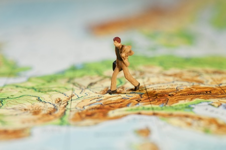 globetrotter: Going The Extra Mile In Business, macro of a miniature model businessman with briefcase striding across a map, concept with shallow DOF.