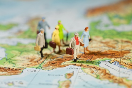 miniature people: European Tourism And Travel, a group of miniature model tourists with luggage on a map of Europe, shallow DOF