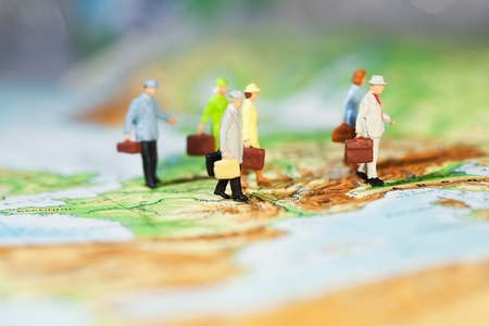 International Business Cooperation, a groupd of miniature businesspeople models walking across a map, low angle and shallw DOF.