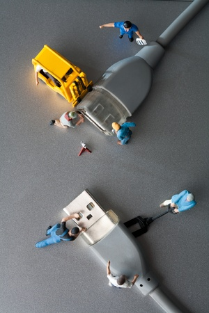 computer cable: Team And Teamwork Concept. An overhead view of a team of miniature toy figurines repairing computer data cables