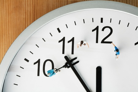 Countdown To Midnight And New Year. A team of miniature toy figurines tries to push the minute hand to midnight, closeup on a portion of a clock face. photo