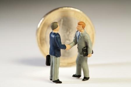 verdrag: Overeenkomst tussen de lidstaten over de Europese schuld. Twee miniatuur beeldjes van zakenlieden elkaar de hand schudden in de voorkant van een rechtopstaande Euro munt op nieuw verdrag voorstellen.