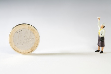 veto: Excercising The Right To Veto. A miniature figurine with his hand in the air facing a Euro coin, conceptual of the UK veto of the EU bailout and restructuring proposals.