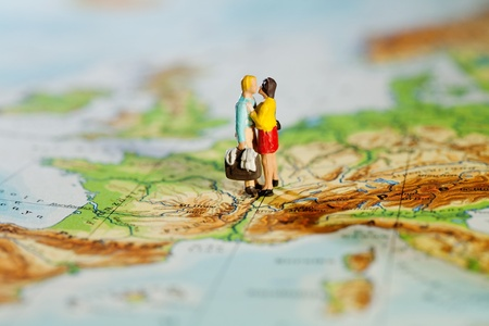Business Or Personal Travel Concept. Two miniature figurines of a man carrying luggage and his wife embracing while standing on a map of Europe. Stock Photo