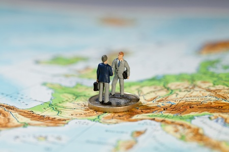 Agreement On New EU Treaty Proposals. Two miniature figurines of businessmen shaking hands standing on a Euro coin on a map of Europe.