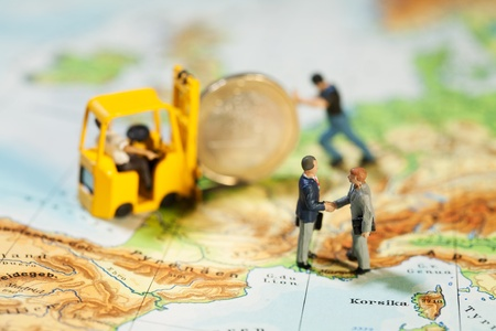 Reaching Accord On European Debt. Twpo miniature figurines of businessmen shaking hands while a Euro coin is loaded on to a forklift, map of Europe, concept. Stock Photo
