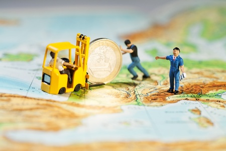 Propping Up The Euro. Team of tiny miniature figurines propping up the Euro and loading it on to a forklift, map of Europe concept.