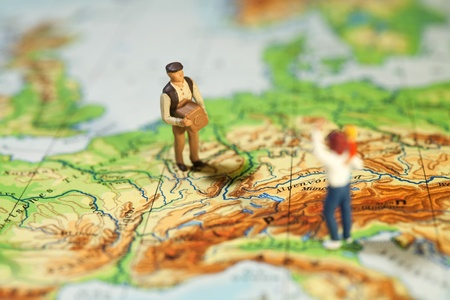 Worldwide Courier Service. A tiny miniature figurine of a man carrying a parcel across a map to a waiting recipient, macro concept. Stock Photo - 11694697
