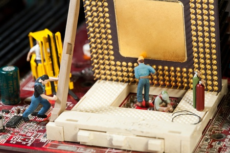 Miniature Maintenance Team. A team of miniature toy figurines busy with repair and maintenance.