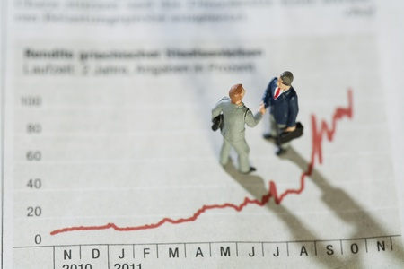 Analysing Annual Monthly Statistics. Two miniature figurines of businessmen having a meeting alongside a fluctuating red line graph showing improving performance over the year. Stock Photo