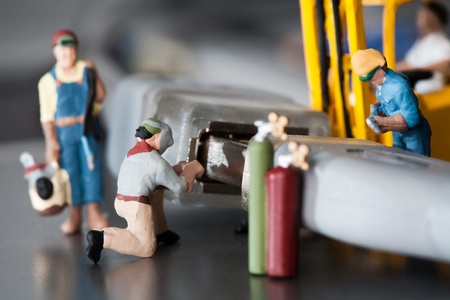 Miniature Artisans Doing Maintenance. A group of tiny miniature artisans working together to repair a cable connection in a teamwork concept