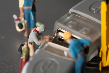 Miniature Artisans Doing Maintenance. A group of tiny miniature artisans working together to repair a cable connection in a teamwork concept photo