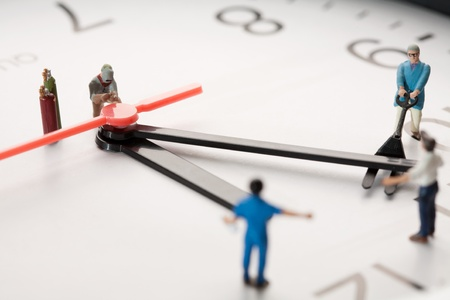 Countdown To Midnight And New Year. A team of miniature toy figurines tries to push the minute hand to midnight, closeup on a portion of a clock face. Stock Photo