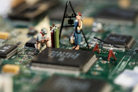 circuitry: Repairing Electronic Circuitry. A miniature model figurine of a welder at work on a circuit board, macro.