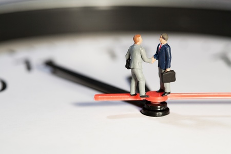 Two miniature businessmen toy models shake hands to seal a business deal while balanced on the hands of a clock, macro side view
