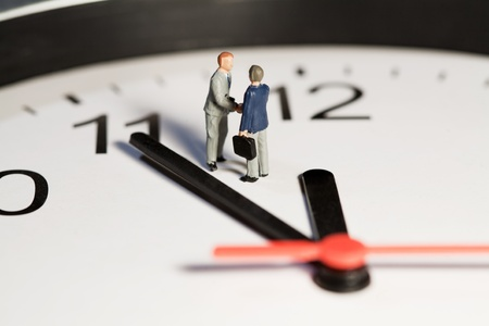 Two miniature businessmen toy models shake hands to seal a business deal while standing on the face of a clock alongside the hands. Stock Photo