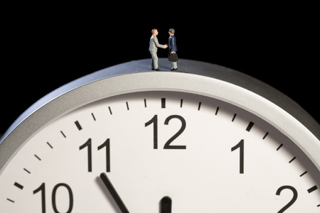 Two tiny model figures of businessmen shaking hands on top of a clock showing the time as five minutes to twelve, horizontal Stock Photo