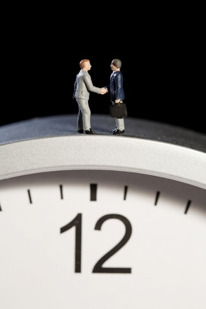 Two tiny model figures of businessmen shaking hands on top of a clock showing the time as five minutes to twelve, vertical.