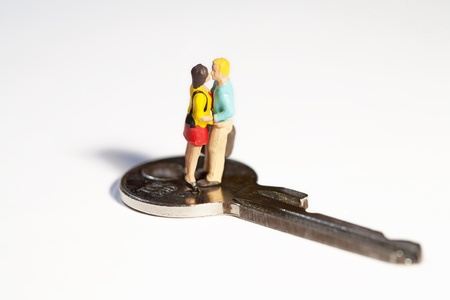 A young couple of miniature toy figures standing in a close embrace on top of a key Stock Photo