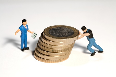 Two miniature workmen figurines moving a pile of Euro coins with their hands.