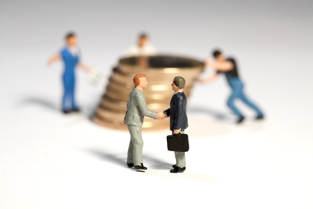 Miniature toy figures of businessmen shaking hands in front of a large pile of Euro coins being moved by workmen, macro with focus to businessmen.