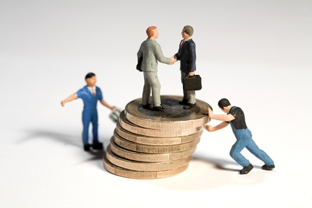 Miniature toy figures of businessmen shaking hands standing on top of of a large pile of Euro coins being moved by workmen Stock Photo