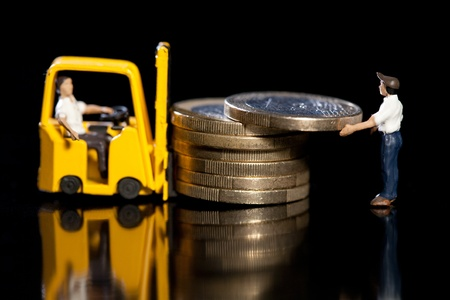Miniature workmen with a forklift load up a pile of Euro coins for removal, macro on black with reflection Stock Photo