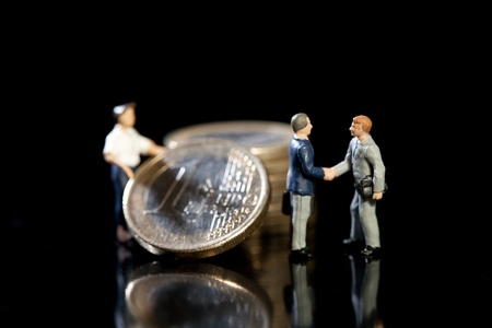 Two miniature toy model businessmen shake hands standing in front of a pile of Euro coins and workman, symbolic of new economic strategy